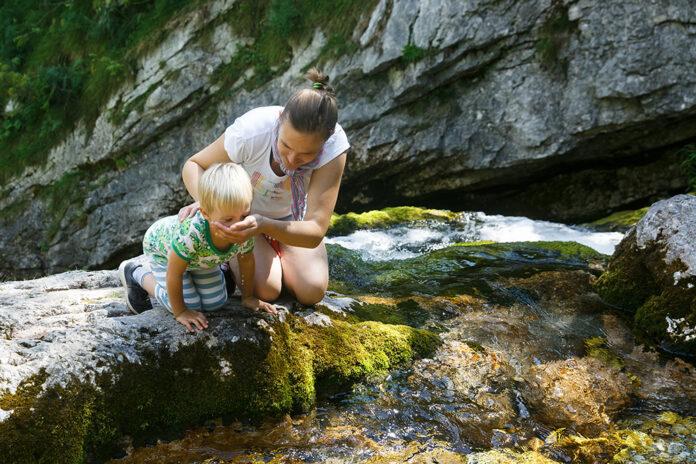 Mamma med son dricker vatten från bäck
